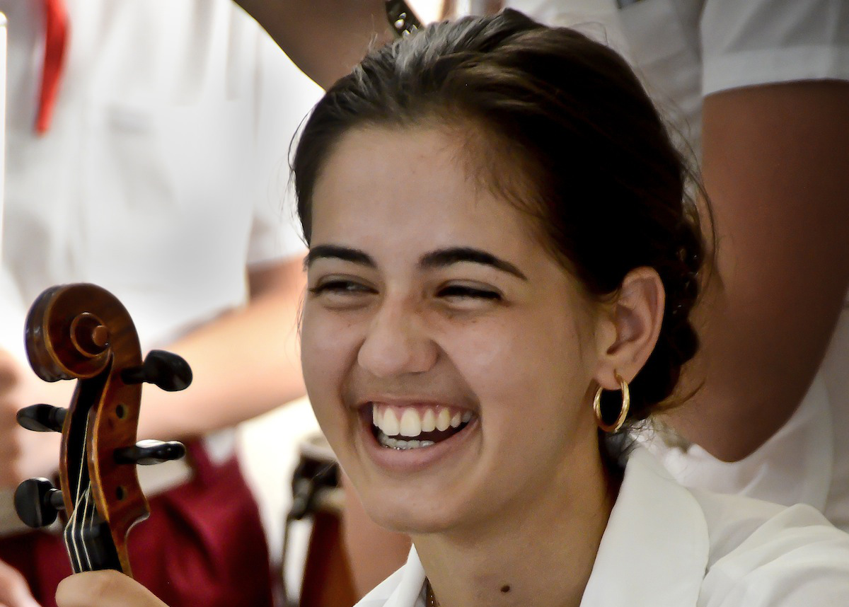 Young Cuban classical music student violinist at Benny More Art School in Cinfuegos smiling